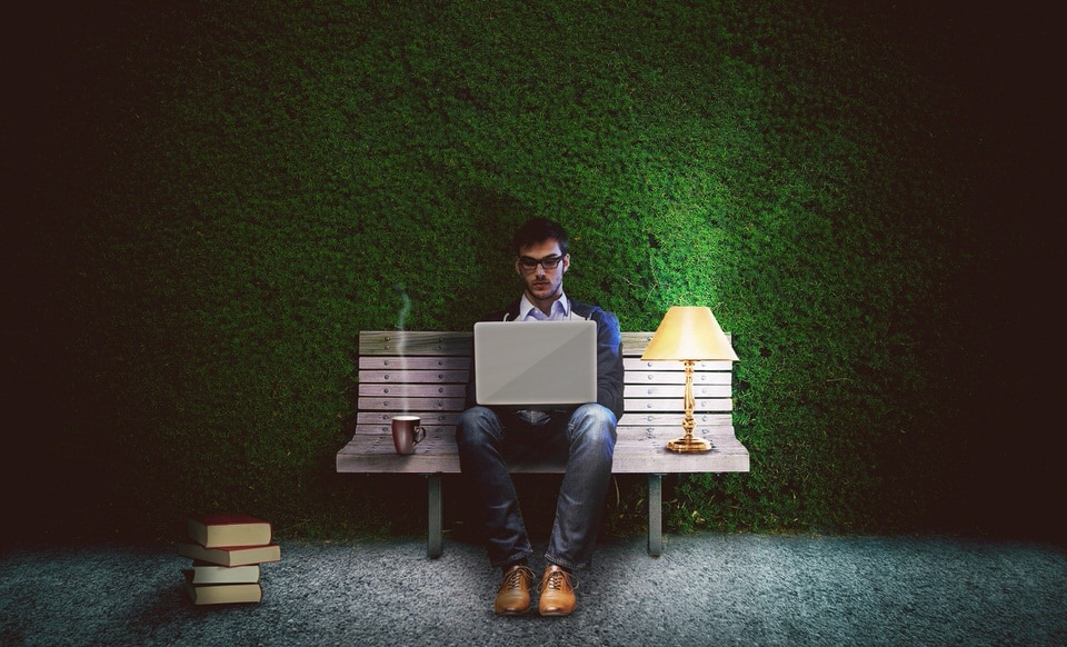 Image of author writing on a laptop while sitting on a park bench.